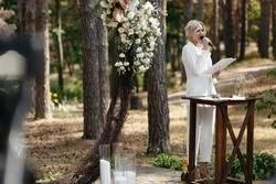 Master of wedding ceremony speeching on microphone on background wedding arch and trees.