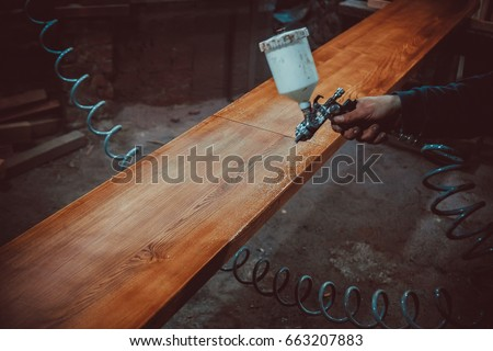 Master painter in a factory - industrial painting  wood with spray gun. #663207883