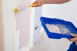 Master plasterer in white t-shirt and blue overall painting the wall in the apartment beige latex paint. Tray for paint roller for painting of premises.
