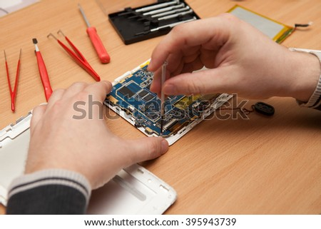 Master repairs the tablet computer. Top view of hands working. #395943739