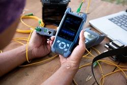 master's hands with optical fiber tester, OTDR meter