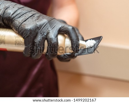 Master spreading foam on black comb, close up view. Preparing for hairstyling. Stylists hands in black rubber gloves. Photographed in barbershop. Selective soft focus. Blurred background