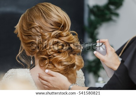 Master stylist makes the bride wedding hairstyle using spray lacquer fixing