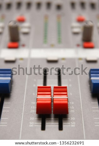 Master volume faders on sound mixer panel in close up.Professional audio equipment for music recording.Regulate volumes on radio broadcasting and night club concert with digital console #1356232691