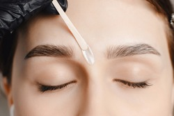 Master wax depilation of eyebrow hair in women, brow correction.