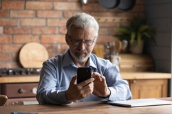 Mastering modern gadget. Focused senior man pensioner in glasses sit by table kitchen hold mobile phone dial number search data online. Serious elderly grandfather make call on cell check email in app