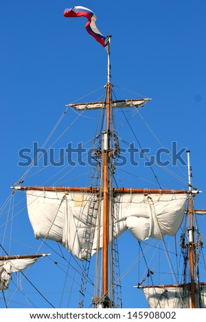 Masts and sails, old sailing ship on the sky background.
