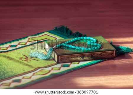 Mat for prayer , the rosary and the holy book the Koran.