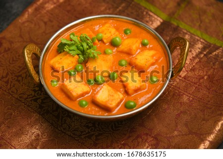 Matar Paneer curry recipe made using cottage cheese, green peas, served in a bowl. selective focus Delhi, Rajasthan India. Top view Indian veg curry on red background. side dish of Roti, Chapati, naan Foto stock ©