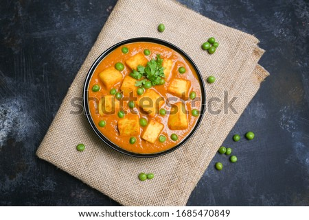 Matar Paneer curry recipe made using cottage cheese, green peas, served in a bowl. selective focus Delhi, Rajasthan India. Top view Indian veg curry on jute background. side dish Roti, Chapati, naan