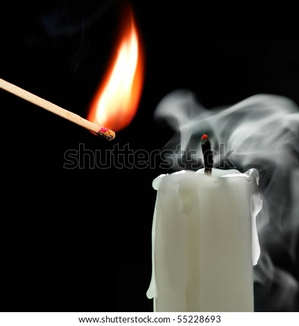 match and candle on a black background
