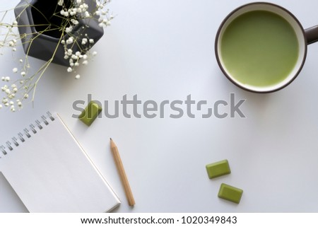 Matcha chocolate, brown cup with green milk tea, notebook, pencil, polygonal grey vase with little white flowers on the light background. Top view, flat lay, copy space, mock up