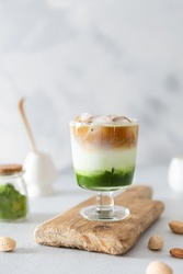 Matcha espresso. Trendy coffee drink with spirulina. Green tea coffee, matcha green tea with milk and coffee. Colorful layer drink. Menu, recipe. Side view, copy space for text