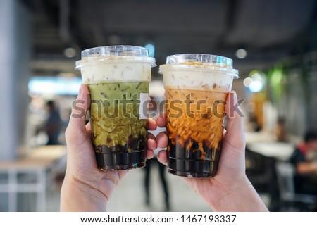 Matcha Green tea and Thai Tea Bubble drinks, man holding a plastic cup of bubble/boba matcha green tea and Thai tea with brown sugar and topped with cheese cream.