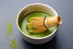 Matcha green tea cooking process in a bowl with bamboo whisk. Grey background. Close up.