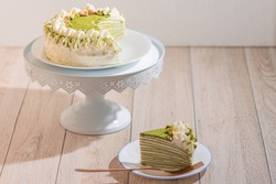 Matcha Mille Crepe Cake Presented On A Cake Holder With A Slice On A Plate