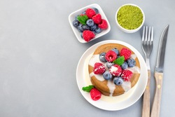 Matcha pancakes served with condensed milk, blueberry and raspberry on a white plate, horizontal, top view, copy space