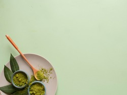 matcha tea on grey plate with spoon and leaf on grean background. Concept healthy drink, copyspace, flatlay, top view