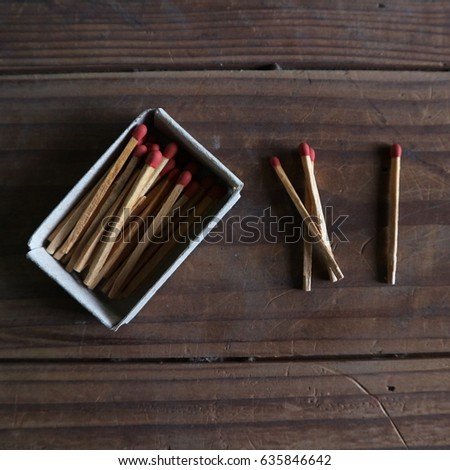 Matchbox, three and one matchsticks placed beside. Vintage Wooden background #635846642