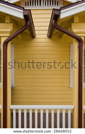 Matched copper rain gutters on the porches of a duplex