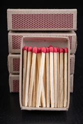 Matches for resurrecting fire in gray boxes. Old methods of lighting a fire. Dark background.