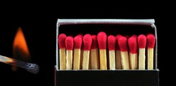 matches isolated on black. burning match and other matches in box. fire hazard.