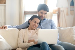 Matching tastes. Loving young husband and wife cuddling on couch at home after workday relaxing resting watching film on laptop computer surfing internet selecting weekend trip on tour company site