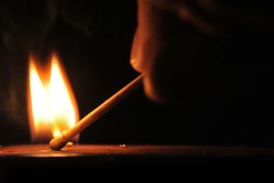 Matchstick ignites with the help of the matchbox with beautiful flames.