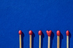Matchsticks with a red heads with heart shaped match among others on a classic blue background. Concept of perfect match, fire of love and passion. The one and only. Flat lay  and copy space.