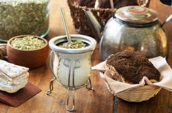 Mate drink over a wooden table with old teapot, pastries and bowl and jar with yerba mate sticked dried leaves