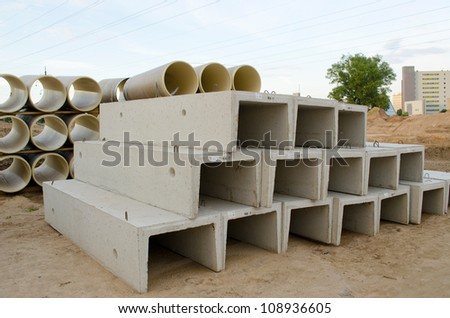 Materials used in road construction works. Concrete molds and plastic sewage pipes.