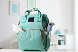 Maternity backpack with baby accessories on table indoors
