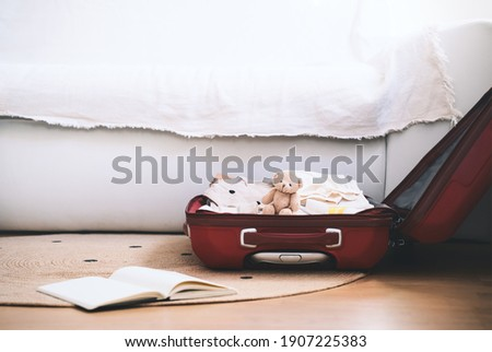 Maternity bag for hospital and paper diary with checking list at home interior. Suitcase of baby clothes and necessities preparing for newborn birth during pregnancy. Photo stock ©