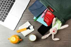 Maternity concept. Female handbag full of different things on office table