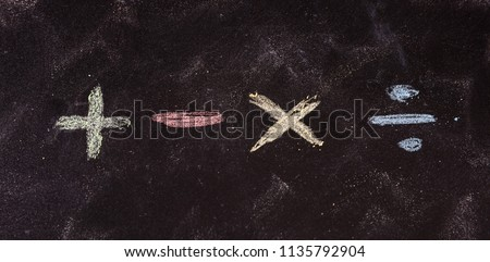 Math concept. Basic mathematical symbols written with colorful chalks, isolated, on blackboard background
