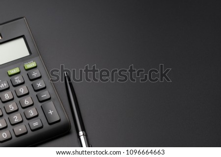 Math, cost, tax or investment calculation, flat lay or top view of black pen with calculator on dark black background table with blank copy space.