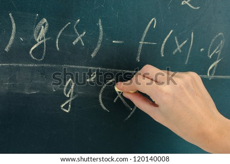 Math formula written on blackboard with chalk.