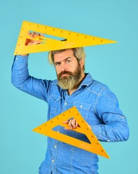Math graphic tools. ready for engineering. tool for graphics. mature bearded man hold triangle ruler. study at home. education. school teacher use triangle. math and geometry subject. back to school.