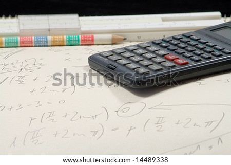 mathematical exercise with pencil ,calculator and sliding rule