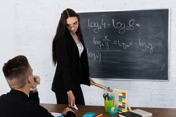 Mathematics problems from the logarithms department. The student is sitting at the school desk. The teacher tells the student to take up the challenge and solve the problem on the blackboard.