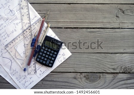 Maths concept background with space for text. Rulers, calculator, pen, compasses and pencil over a sheet of paper with maths-formulas. Mathematical analysis, probability theory. Complex analysis.