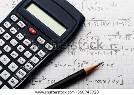 Maths concept - handheld calculator and pencil over a sheet of paper with maths-formulas
