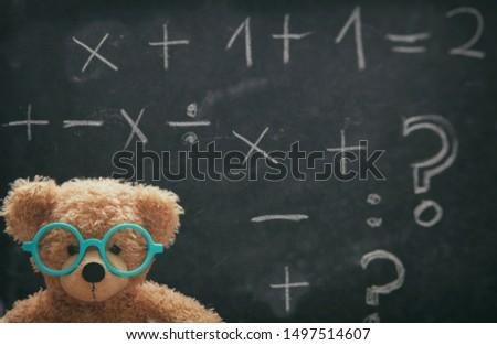 Maths concept. Smart kid in school class, cute teddy wearing blue eyeglasses and math symbols on blackboard