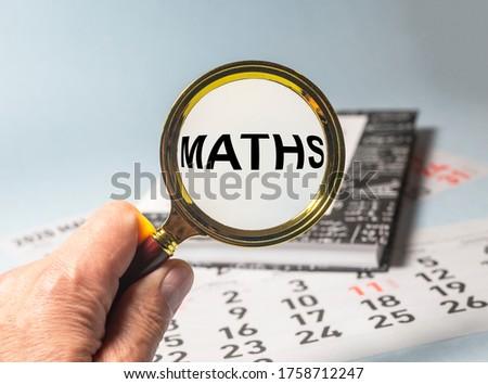MATHS word inscription through magnifier glasson book of maths on blue table and calendar. educational maths concept. maths study concept