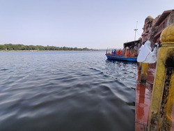 Mathura Yamuna River Bank with boats and clear water.A holy dip awaited.
