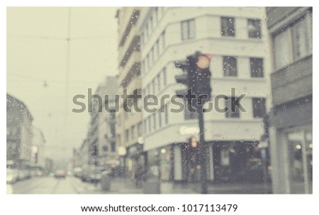 Matte Vintage. Snowy day in the city. Retro style. Drive. Traffic light. Overcast. Houses and a road. Blurred avenue scene. Blur urban background. Old photo