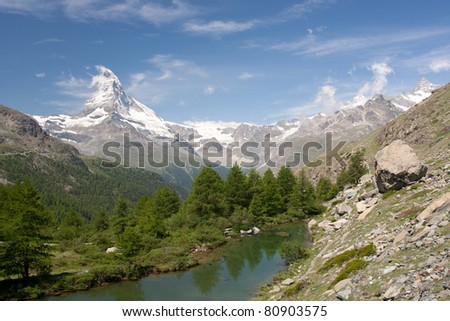 Matterhorn mountain with morning clouds reflecting in Moosjisee, Alps, Switzerland