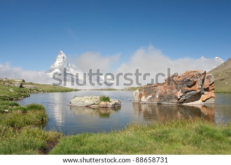 Matterhorn mountain with morning clouds reflecting in Stellisee, Alps, Switzerland