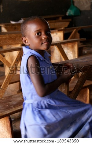 MATUGGA, UGANDA, AFRICA - CA AUGUST 2013: Unidentified young girl in a blue school uniform sitting on an old fashioned wooden school bench in a classroom. North of Capital Kampala, Uganda, East Africa