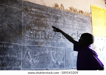 MATUGGA, UGANDA, AFRICA - CIRCA AUGUST 2013: Unidentified young boy in a purple school uniform pointing at the blackboard, reading out loud what he learned today. North of Kampala, Uganda, East Africa